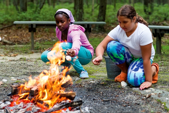 Girls cooking over fire